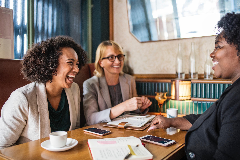 Three women laughing at a coffee shop —dreams need teams blog