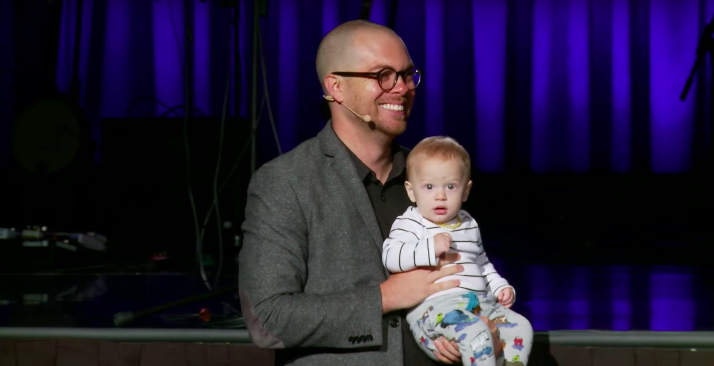 Chase holding his son Silas while preaching